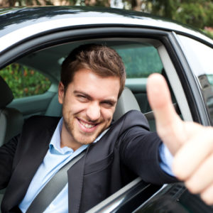 Man giving a thumbs up while driving his brand new free car