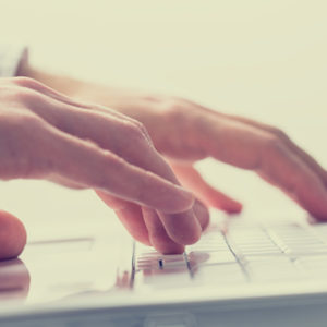 A transcriptionist typing on a keyboard